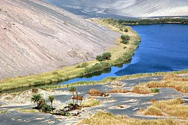 Blue lake surrounded by green-yellow vegetation, within a desert and at the foot of a hill