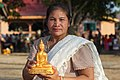 Women holding a statue of the Buddha in Laos.jpg
