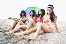 Four dark-haired women tanning on a beach. A rainbow sun umbrella is somewhat visible behind them
