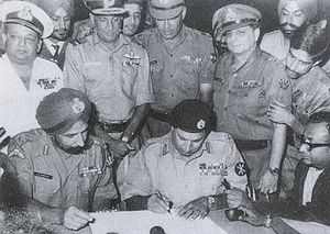 Pakistani Instrument of Surrender - Lt Gen A A K Niazi signing the Instrument of Surrender under the gaze of Lt Gen J S Aurora. Standing immediately behind (L-R) Vice Admiral Krishnan, Air Marshal Dewan, Lt. Gen Sagat Singh, Maj Gen JFR Jacob (with Flt Lt Krishnamurthy peeping over his shoulder). Veteran newscaster, Surojit Sen of All India Radio, is seen holding a microphone on the right.