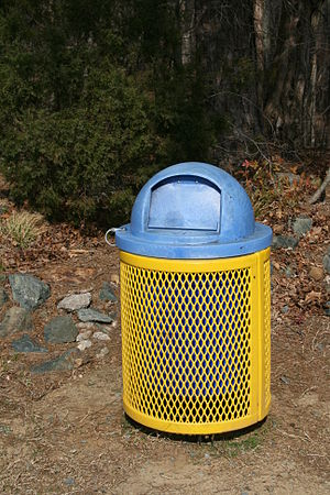 English: A yellow metal trash can with a blue ...