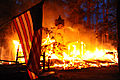 A U.S. flag hangs in front of a burning structure in Black Forest, Colo., June 12, 2013 130612-F-CD000-031.jpg