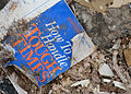 A booklet (How to Handle Tough Times by Norman Vincent Peale) lies amid debris 130526-Z-TK779-009.jpg