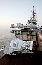 An F/A-18C on an aircraft elevator of the USS Kitty Hawk