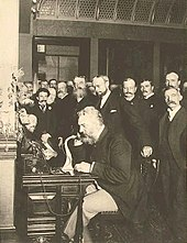 A grizzly and well-dressed Alexander Graham Bell sits at a desk talking over a candle-stick telephone, surrounded by numerous business executives and news reporters who are witnessing a historic event in the atrium of a large corporate building.