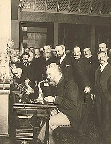 A grizzly and well-dressed Alexander Graham Bell sits at a desk talking over antique telephone, surrounded by numerous business executives and news reporters, who are witnessing a historic event, in the atrium of a large corporate building.