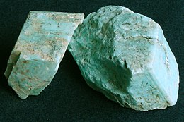 Photo of a turquoise mineral with beige microcline speckled within it