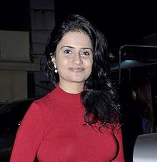 Snap of a woman in red top, smiling at the camera, with hair on left shoulder.
