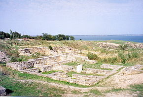 Remains of walls of small structures are seen in the foreground, while the Southern Bug estuary is seen in the background.