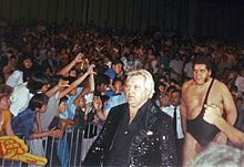 Bobby Heenan (front), a Caucasian man in a black sequin jacket, leads André the Giant to the ring