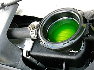 Antifreeze - Fluorescent green-dyed antifreeze is visible in the radiator header tank when car radiator cap is removed