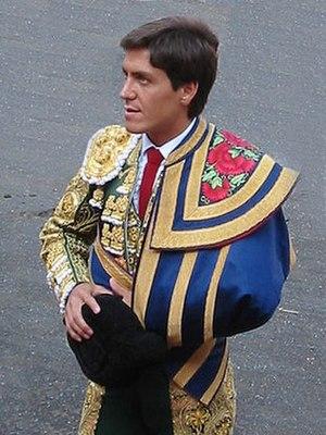 Traje de luces - Torero Antonio Barrera dressed in a traje de luces with the ceremonial capote de paseo over his left arm and the montera in his right hand