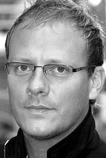 Greyscale photograph of a blond man with glasses