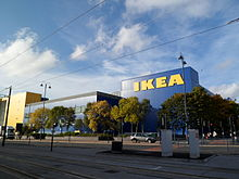 "A blue building with ""Ikea"" written on the side in large yellow letters. Trees in the foreground."