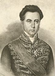 Lithographic half-length portrait of a man with dark hair and wearing a sash of office and medals over an intricately embroidered tunic coat