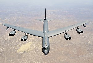Aerial top/side view of gray B-52H flying over Texas