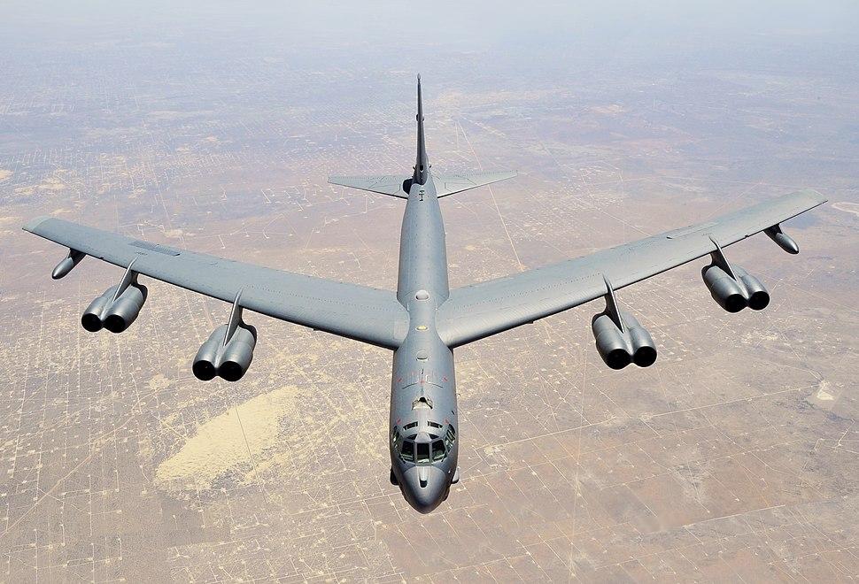 Aerial top/side view of gray B-52H flying over barren desert land.