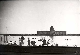 Saskatchewan Legislative Building - People enjoying a boat race on Wascana Lake north of the Legislative Building circa 1910.