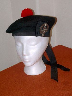 Balmoral bonnet - A modern Balmoral in black wool, with black grosgrain headband, cockade and ribbons, a red yarn toorie, and a clan crest badge on the cockade