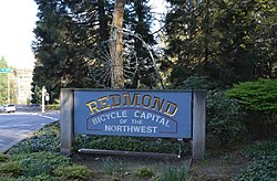 "Welcome sign on Redmond Way readign ""Redmond: Bicycle capital of the northwest"" and featuring a pennyfarthing bicycle atop the written portion of the sign"