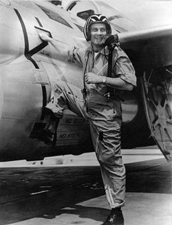 A monochrome photograph of an energetic man in his 30s wearing a jet pilot uniform and helmet, stepping with one booted foot up onto a military jet, his right hand on the jet, turning back to smile at the viewer