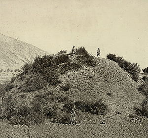 History of Kashmir - This general view of the unexcavated Buddhist stupa near Baramulla, with two figures standing on the summit, and another at the base with measuring scales, was taken by John Burke in 1868.  The stupa, which was later excavated, dates to 500 CE.