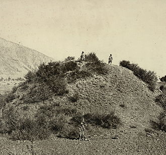 Kashmir - This general view of the unexcavated Buddhist stupa near Baramulla, with two figures standing on the summit, and another at the base with measuring scales, was taken by John Burke in 1868. The stupa, which was later excavated, dates to 500 CE.