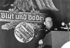 Blood and Soil - Richard Walther Darré addressing a meeting of the farming community in Goslar on 13 December 1937 standing in front of a Reichsadler and Swastika crossed with a sword and wheat sheaf labelled Blood and Soil (from the German Federal Archive)