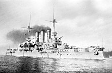 A large light gray battleship sits in harbor, smoke drifts up from its three tall funnels