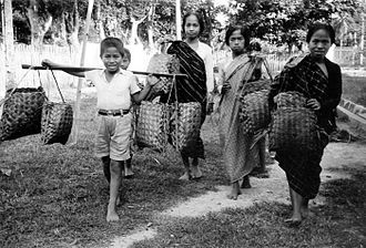 West Sulawesi - Three women and two boys from West Sulawesi sell charcoal. Colonial period, 1937.