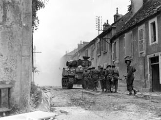Operation Tractable - Canadian troops with armour support advance cautiously through the streets of Falaise, encountering only light scattered resistance.
