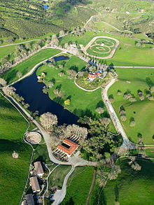 Aerial photograph of an estate with a racetrack visible in the background