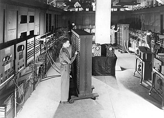ENIAC - Cpl. Irwin Goldstein (foreground) sets the switches on one of ENIAC's function tables at the Moore School of Electrical Engineering. (U.S. Army photo)