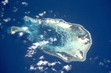 An overhead photograph showing the same atoll with its large lagoon reaching into the island's interior.