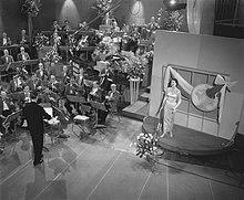 Schwarzes Foto während des Wettbewerbs von 1958 in den AVRO Studios in Hilversum, Niederlande;  Links von einer kleinen Bühne sitzt ein Orchester unter der Leitung von Dolf van der Linden. Der niederländische Sänger Corry Brokken singt auf der Bühnenplattform vor einer Wand.