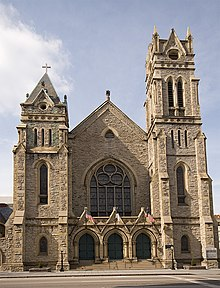 Exterior of Gothic style church built from handcut stone with a bell tower.