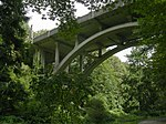 An art deco styled concrete bridge over a wooded ravine