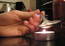 un cucchiaino contenente cocaina e bicarbonato su una fonte di calore candela che necessaria per far proseguire la reazione