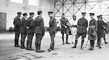 A group of military personnel in an aircraft hangar, four of whom are in a row facing another man, while the remainder stand informally, one of them wearing a flying suit