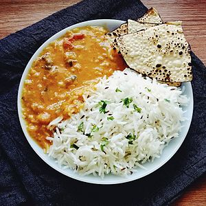 Dal - Dal tadka served with rice and papadam, staple meal in South Asia.
