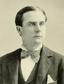 A man with black hair wearing a black jacket and vest, patterned bowtie and white shirt and pocket square