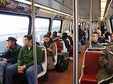 Los pasajeros se sientan en unidades fijas de dos asientos.  Hay postes y barras de metal para que las personas de pie las sostengan.