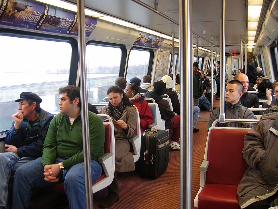 Passengers sit in fixed two-seat units. There are metal poles and bars for standees to hold.