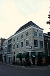 foto van Hoekpand, hoog schilddak, bovendeel van een rijkversierde renaissance gevel met speklagen, ontlastingsbogen met sluitstenen