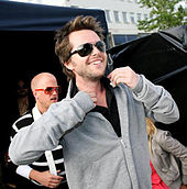 A picture of a man with dark hair wearing sunglasses and a grey top