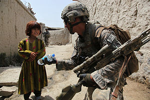 A U.S. Soldier hands an Afghan girl a bottle o...