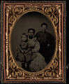 Full length group of three; black woman seated with white child in lap, white boy stands with hand on her shoulder. Cased tintype, quarter plate.jpg