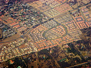 Bird's-eye view of residential neighborhoods. The houses at the bottom third of the picture have much larger yards and more trees. The neighborhood in the center of the picture has a very defined road shaped like a backwards 6, and the houses have orange and grey roofs and are very close to each other. The neighborhood at the top right has multicolor roofs. There is a road cutting through the middle of the picture.