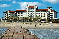 A stately white hotel building with a red-tile roof is seen from the end of a jetty extending from the beach.