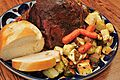 Garlic braised pork roast with roasted veggies and whole clove garlic bread (6792699277).jpg